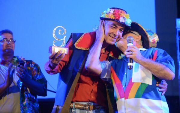 Carlos Lira recebe o afeto e o troféu do coordenador do Janeiro de Grandes Espetáculo, por seus 40 anos de carreira